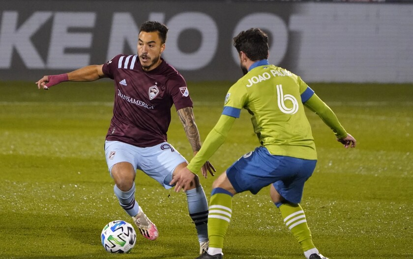 Colorado Rapids forward Andre Shinyashiki, left, works the ball past Seattle Sounders midfielder Joao Paulo in the first half of an MLS soccer match Sunday, Nov. 1, 2020, in Commerce City, Colo. (AP Photo/David Zalubowski)
