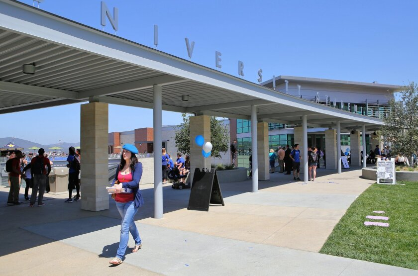 Cal State University San Marcos students make their way past the front of the new student union building at the university.