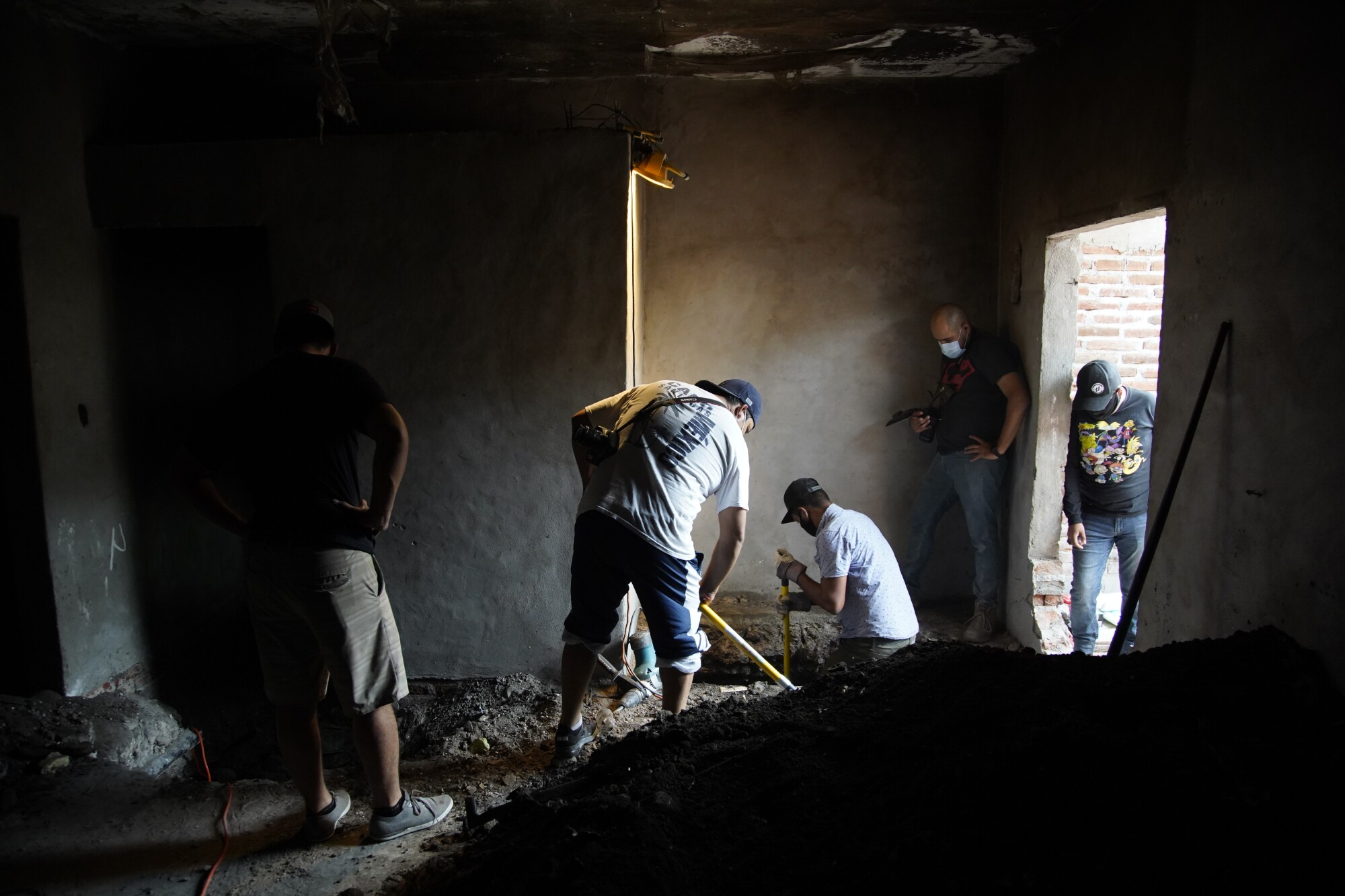 People dig for bodies inside a house.