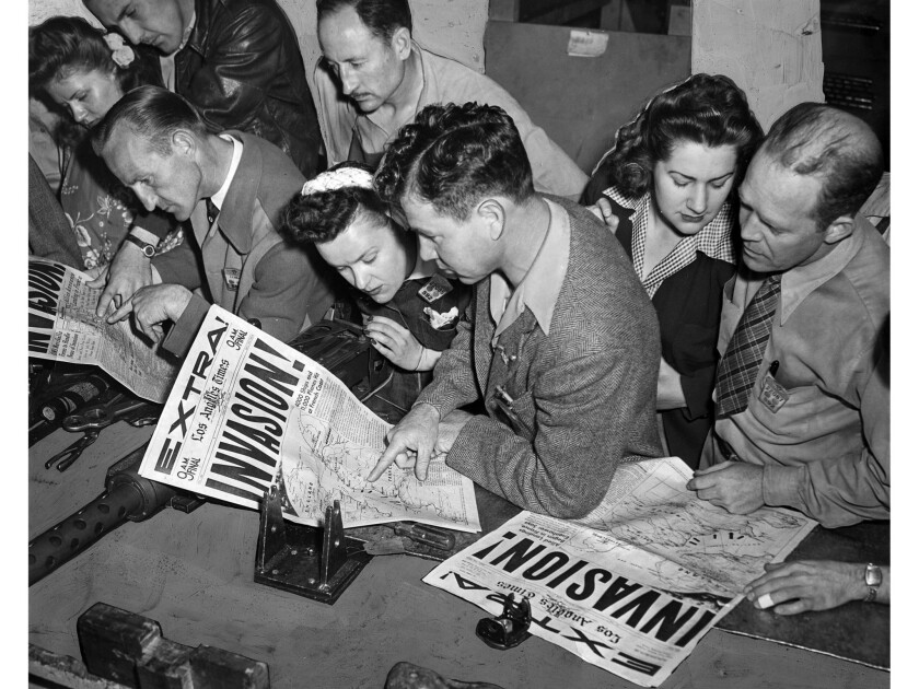 June 6, 1944: Workers in armament room of Douglas Aircraft Co., read about D-Day invasion news in th
