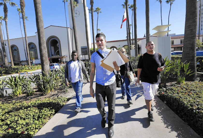 Clients of youth housing and service agency Jovenes walk through Union Station seeking people 24 and younger to count in L.A.'s official homeless tally.