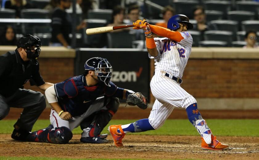 El torpedero de los Mets de Nueva York Francisco Lindor pega un sencillo productor en la octava entrada del juego ante los Bravos de Atlanta, el miércoles 23 de junio de 2021, en Nueva York. (AP Foto/Noah K. Murray)