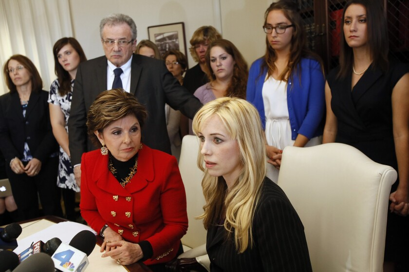 """Attorney Gloria Allred, left sitting and Dr. Caroline Heldman, professor of politics, along with 6 sexual assault victims at a news conference last April to announce the filing of a complaint against Occidental as a result of what the women allege is the college's """"Deliberate indifference to rape victims."""""""