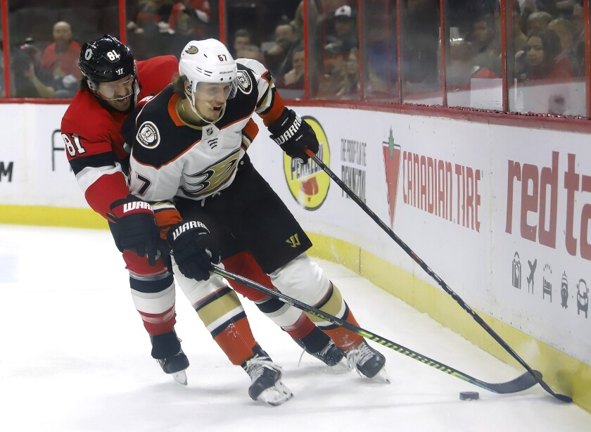 Ducks left wing Rickard Rakell and Senators center Chris Tierney battle along the boards during the first period of a game Feb. 4.