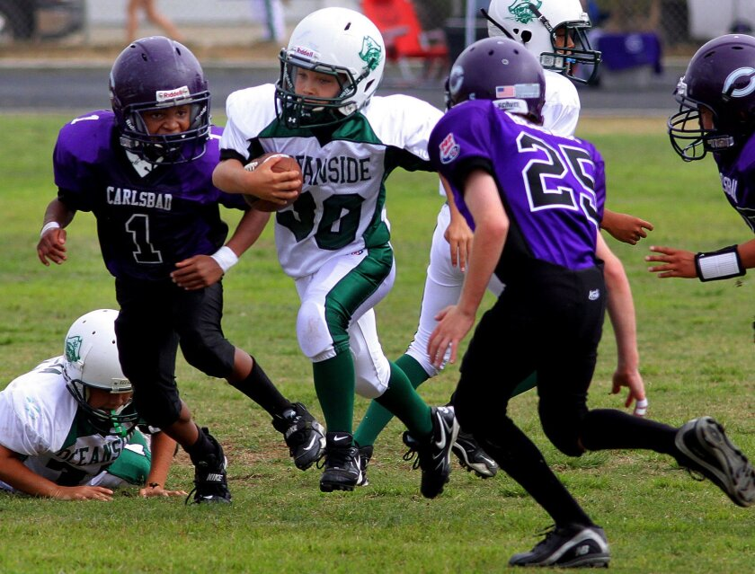 Diego McFayden of the Oceanside Pirates Junior PeeWee Pop Warner team runs the ball up the middle as Carlsbad Lancers defenders Tyler Cross (No. 1) and Tyler Hershey (25) try to close the gap during a Pop Warner game in Carlsbad last weekend. Oceanside won the contest, 18-12.