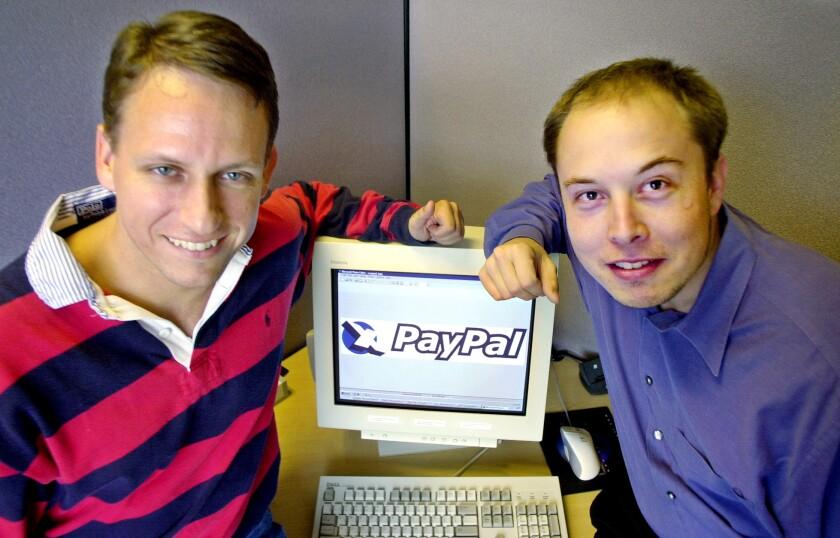 مردی با پیراهن راه راه و مردی روی دکمه ها روی مانیتور کامپیوتر تکیه داده اند.