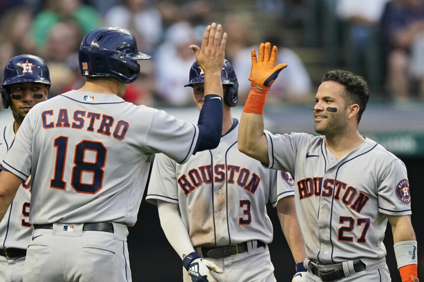 Houston Astros' Jose Altuve (27) is congratulated by Jason Castro (18) after Altuve hit a grand slam in the fifth inning of a baseball game against the Cleveland Indians, Thursday, July 1, 2021, in Cleveland. (AP Photo/Tony Dejak)