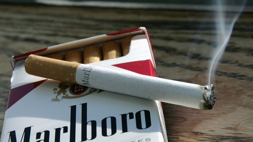 A cigarette burns on top of a pack.