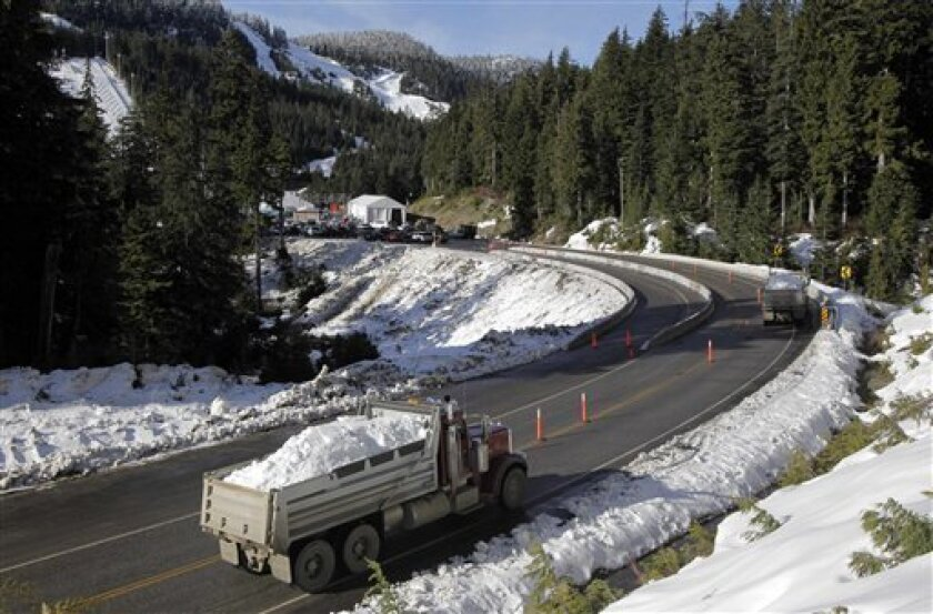 Trucks carrying snow drive along the road at Cypress Mountain, a venue for freestyle skiing and snowboard, in West Vancouver, British Columbia, Thursday, Feb. 4, 2010. The Vancouver 2010 Olympic Games begin Friday, Feb. 12. (AP Photo/Jae C. Hong)