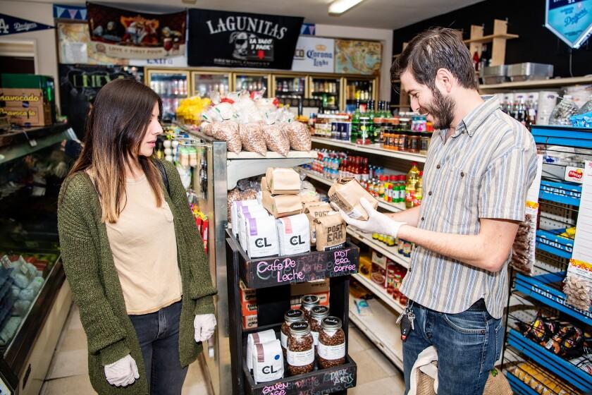 Elis Hoyos and Leo Abularach, co-owners of local company Post Era, refill the display at Sara's Market.