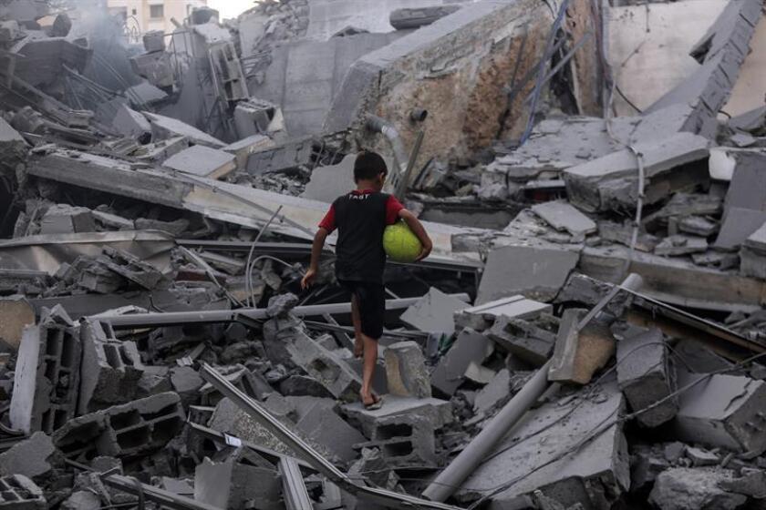 Un niño palestino juega en los restos de un centro cultural destruido por un ataque aéreo israelí en Gaza (Palestina ). EFE/Archivo