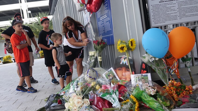 The Lopez family of Miami places balloons at a memorial in front of Marlins Park on Sunday.