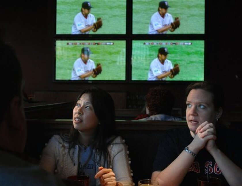 Doris Chin, of Medford, Mass., left, and Anne Devoy, of Somerville, Mass., right, watch Boston Red Sox pitcher Daisuke Matsuzaka throw against the Oakland Athletics from the Game On! pub at Fenway Park in Boston, during the opening game of the 2008 Major League baseball season at Tokyo Dome in Tokyo, Japan Tuesday, March 25, 2008. (AP Photo/Josh Reynolds)