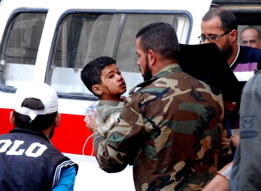 A soldier carries a wounded child after a car bomb attack at a mosque in Wadi Barada, near Damascus, on Oct. 25, 2013.