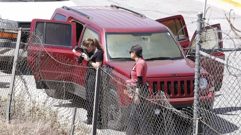 Investigators take photographs near a vehicle in Burbank where police found three dead bodies on Tuesday, April 17. Coroner's officials have confirmed two of the victims died of gunshot wounds to the head.