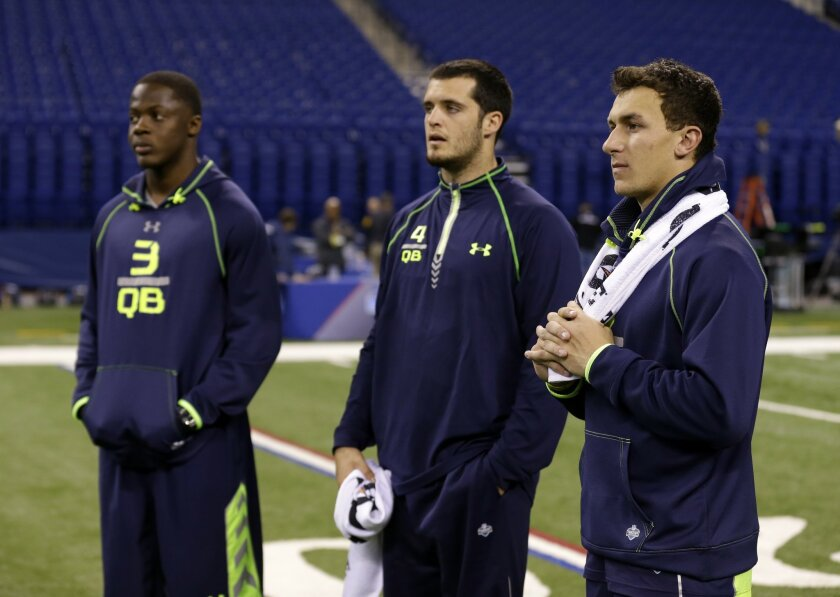 Texas A&M quarterback Johnny Manziel, right, Fresno State quarterback Derek Carr, center, and Louisville quarterback Teddy Bridgewater watch drills at the NFL football scouting combine in Indianapolis, Sunday, Feb. 23, 2014. (AP Photo/Michael Conroy)