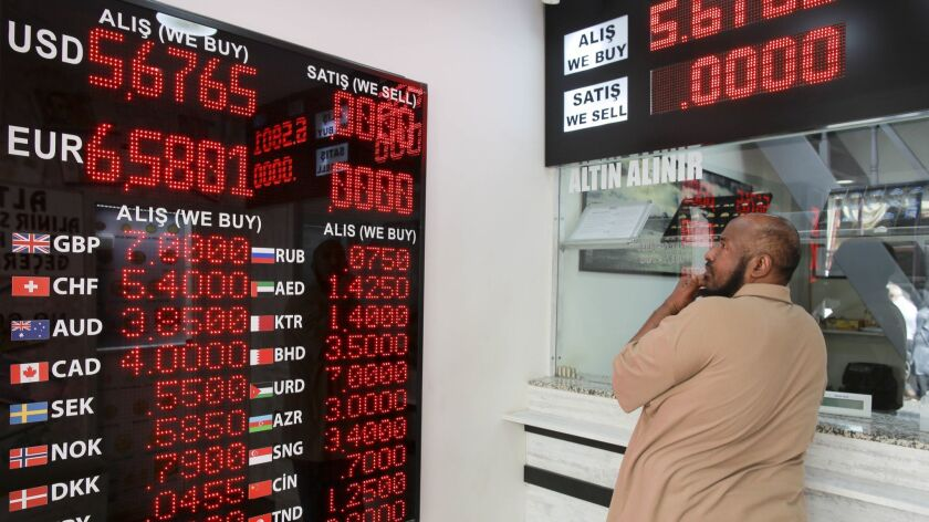 A man checks foreign currency exchange rates in Istanbul after financial shockwaves ripped through Turkey on Friday after its currency nose-dived on concerns about its economic policies and a dispute with President Trump