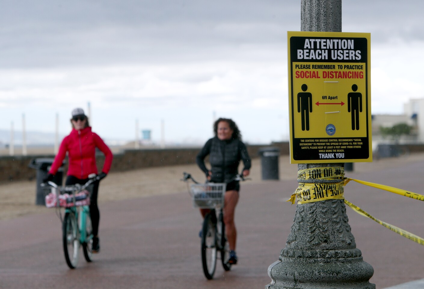 Bicycle riders practice social distancing just north of the Huntington Beach pier, in Huntington Beach on Friday, April 10, 2020.