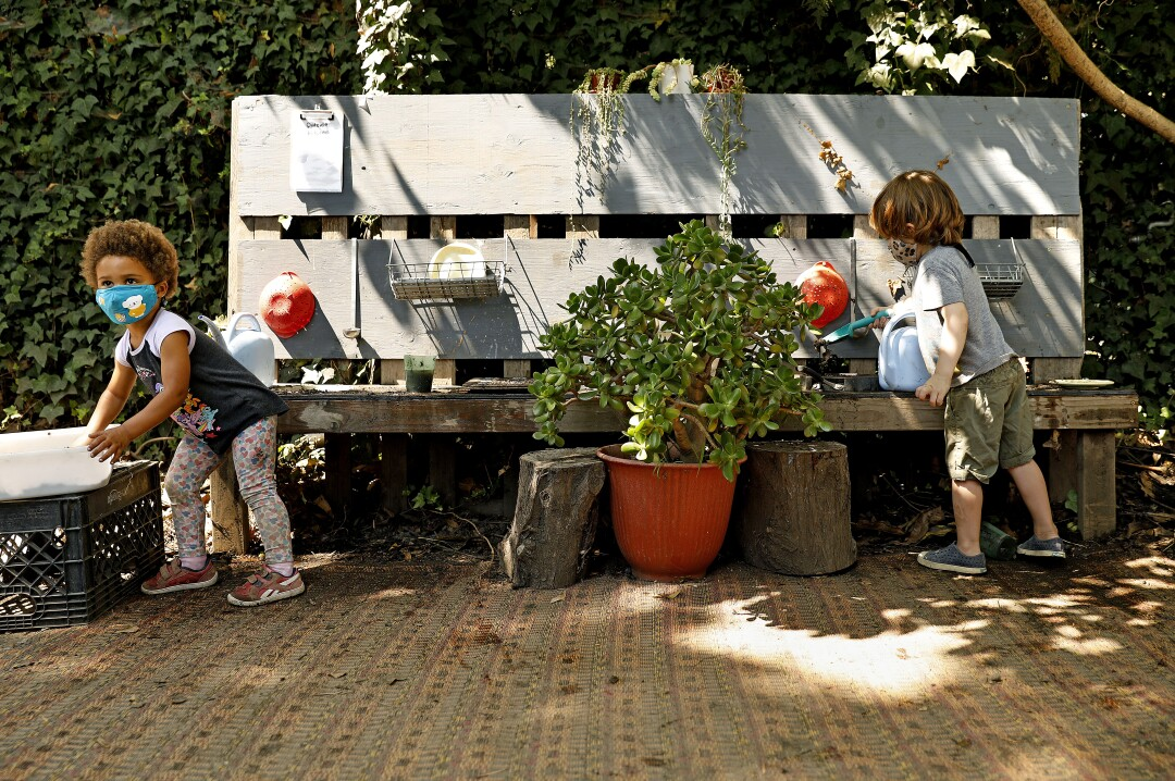Children socially distance while playing in an outdoor kitchen at Voyages Preschool.