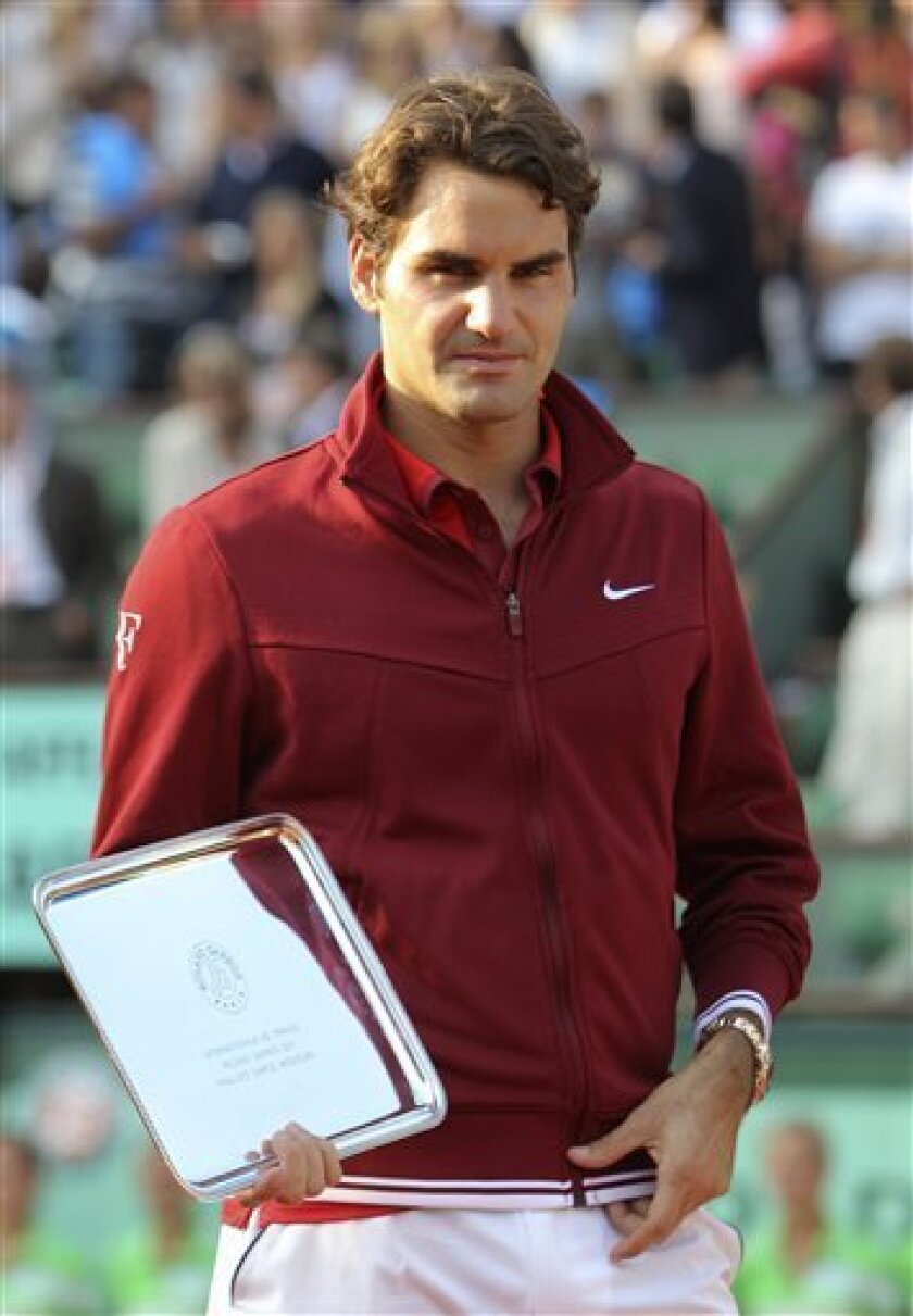 Switzerland's Roger Federer holds his trophy after losing to Spain's Rafael Nadal in the men's final match for the French Open tennis tournament at the Roland Garros stadium, Sunday, June 5, 2011, in Paris. (AP Photo/Michel Euler)