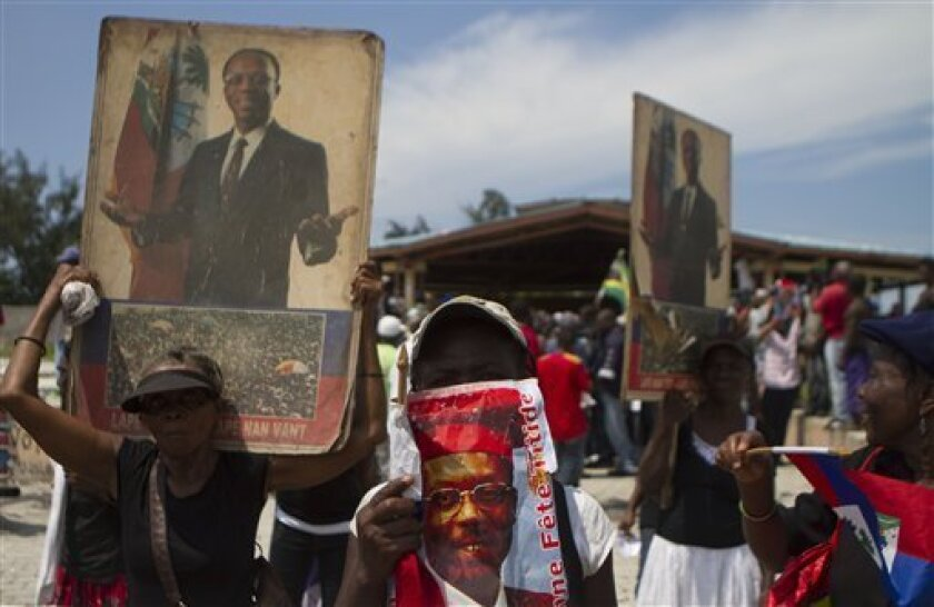 Supporters of Haiti's former President Jean-Bertrand Aristide hold portraits of him during a rally marking the 20th anniversary of a military coup that ousted Aristide in 1991 in Port-au-Prince, Haiti, Friday Sept. 30, 2011. (AP Photo/Dieu Nalio Chery)