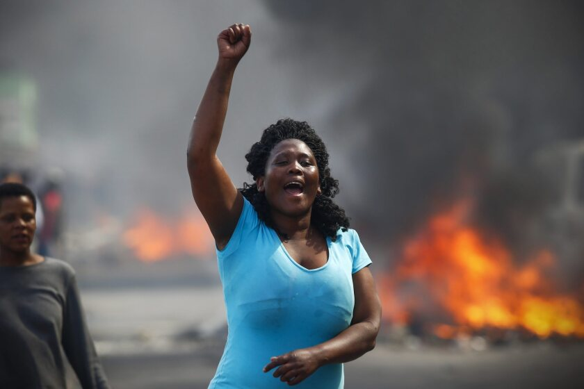 A woman shouts Tuesday during a protest over the lack of policing in the township of Masiphumelele, Cape Town, South Africa.
