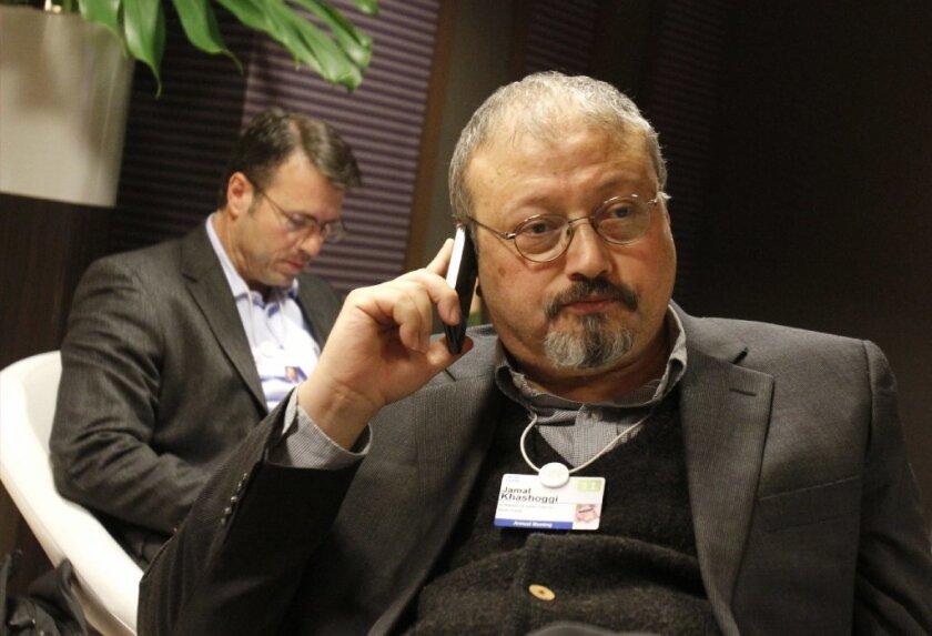 FILE - In this Jan. 29, 2011 file photo, Saudi journalist Jamal Khashoggi speaks on his cellphone at the World Economic Forum in Davos, Switzerland.