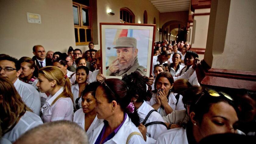 Médicos cubanos que trabajan en Venezuela sostienen una foto de Fidel Castro durante un tributo organizado después de su muerte, en noviembre pasado (Fernando Llano / Associated Press).