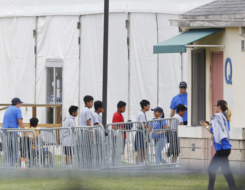 Immigrant children walk in a line outside a shelter