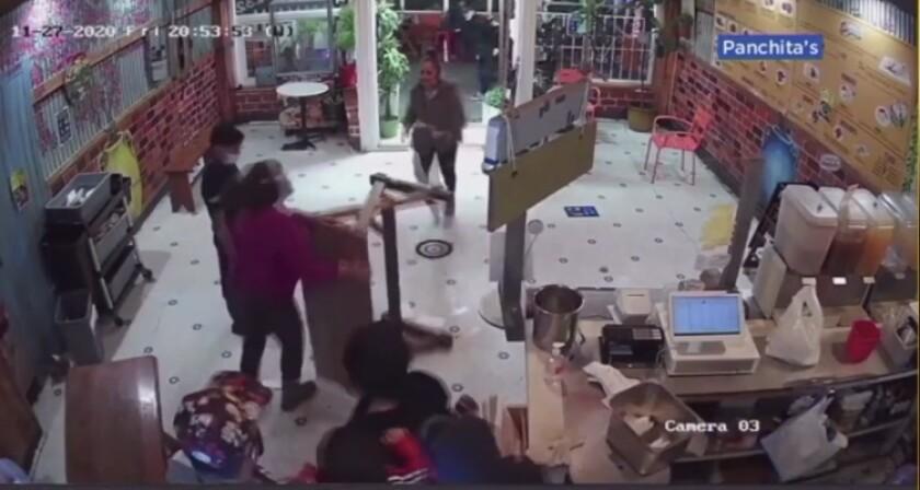 En esta imagen se observa a Doris Campos (camisa ocre) empujar una mesa en contra de una mujer agresiva.
