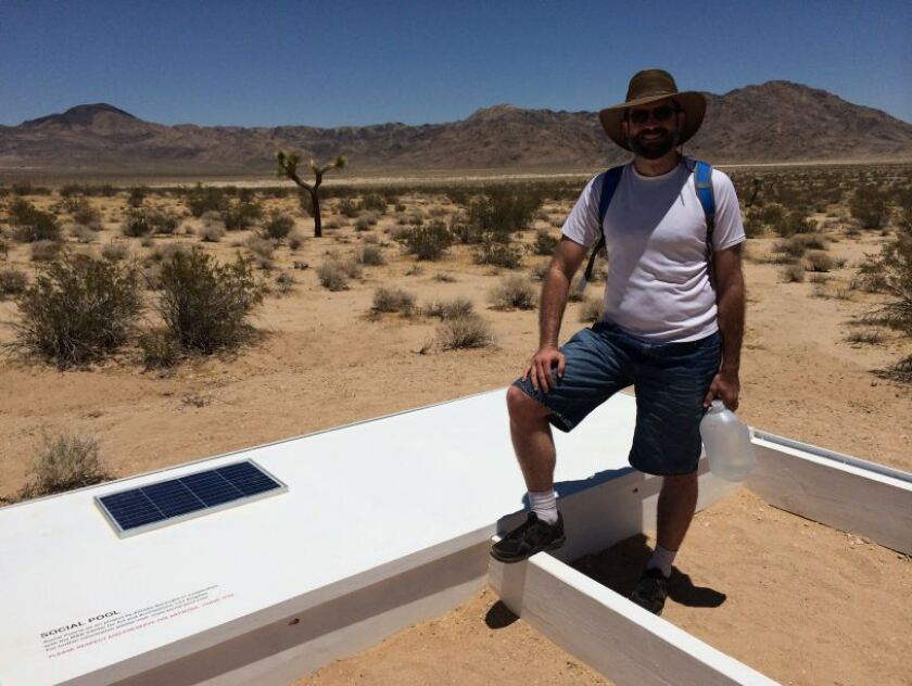 "Steven J. Lewis arrives at ""Social Pool,"" artist Alfredo Barsuglia's diminutive pool in the Mojave Desert. He brings a gallon of water to help replenish what's lost from evaporation and use."