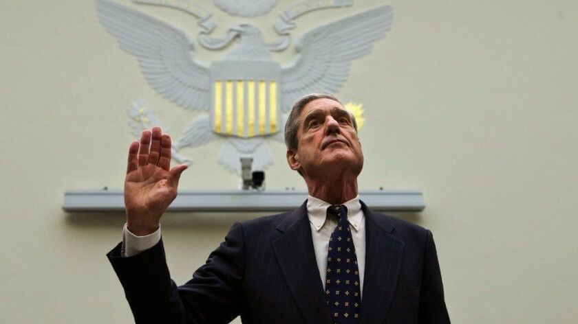 Robert S. Mueller III raises his right hand to take an oath in 2013.