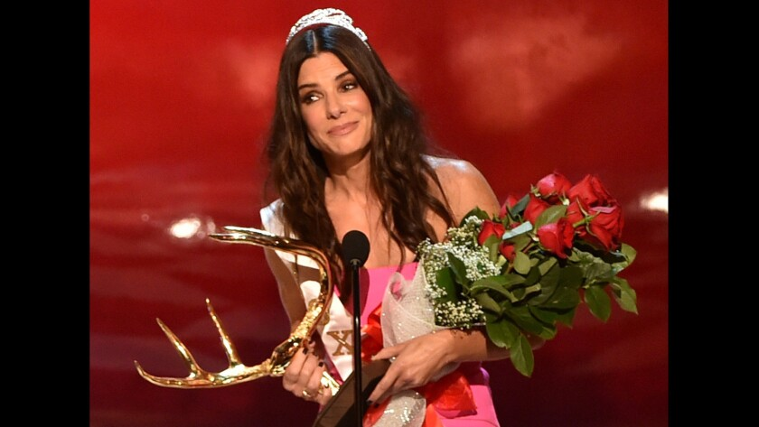 """Sandra Bullock, who topped Forbes' 2014 list of top-earning actresses, accepts the """"decade of hotness"""" award at Spike TV's Guys Choice 2014 event in June."""