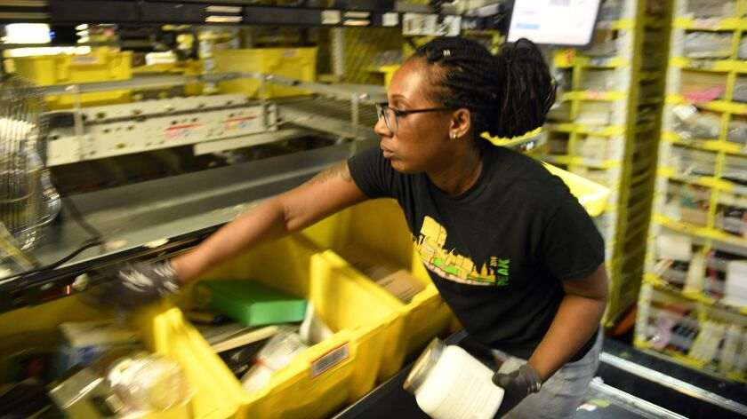 Worker Jackie Spence places ordered products into bins at an Amazon warehouse in Baltimore in May.