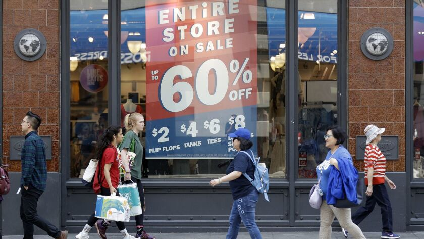 Shoppers in San Francisco walk past a store advertising discounts on July 3.