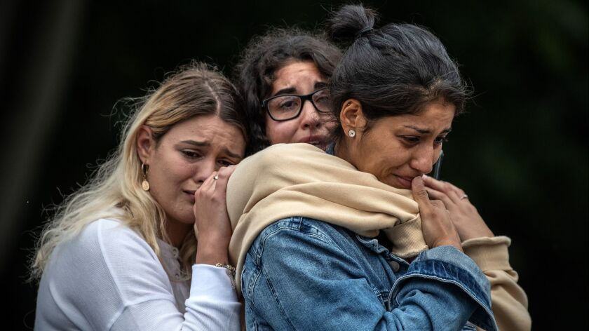 Women weep together near Al Noor mosque in Christchurch, New Zealand, on Monday. A terrorist attack on two mosques last week killed at least 50 people.