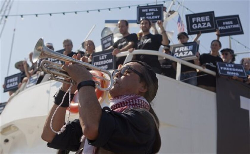 """An activist plays a trumpet as others hold banners on their boat named """"Audacity of Hope"""" moored in Perama, near Athens, Greece, Thursday, June 30, 2011. Organizers of a pro-Palestinian flotilla that will try to break Israel's sea blockade of the Gaza Strip accused Israel of sabotaging a second ship. (AP Photo/Darko Bandic)"""