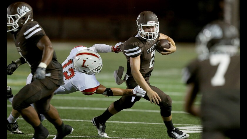 Crespi quarterback Hamish McClure eludes the grasp of Orange Lutheran linebacker T.J. Augustin in a game on Sept. 4, 2015.