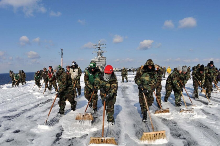 WESTERN PACIFIC OCEAN (March 23, 2011) - Sailors assigned to the aircraft carrier USS Ronald Reagan (CVN 76) and Carrier Air Wing (CVW) 14 man their brooms during a counter-measure wash down on the flight deck. Crewmembers scrubbed the external surfaces on the flight deck and island superstructure