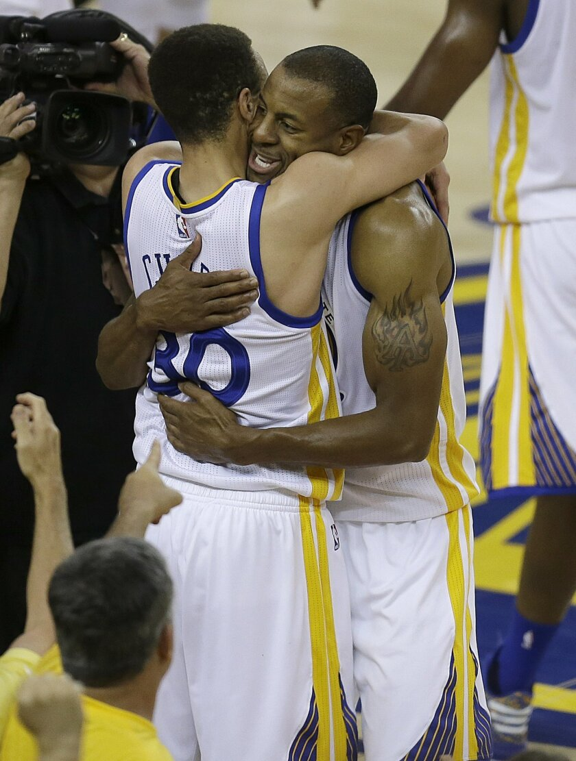 Golden State Warriors guard Stephen Curry (30) hugs forward Andre Iguodala (9) after the Warriors beat the Oklahoma City Thunder in Game 7 of the NBA basketball Western Conference finals in Oakland, Calif., Monday, May 30, 2016. The Warriors won 96-88. (AP Photo/Ben Margot)
