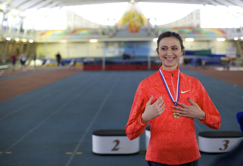 Russia's Maria Kuchina smiles with her gold medal after winning the women's high jump competition at a Russian Grand Prix track and field indoor event in Moscow, Russia, on Friday, Jan. 22, 2016. Just five months ago, Maria Kuchina won the world high jump title in front of tens of thousands of fans in Beijing. On Friday, she jumped at a meet with a few dozen athletes and fewer spectators. Russia's ban from global track and field over doping has forced some of the world's top athletes to compete at obscure domestic events with tiny crowds, rather than prestigious and lucrative international meets. (AP Photo/Ivan Sekretarev)