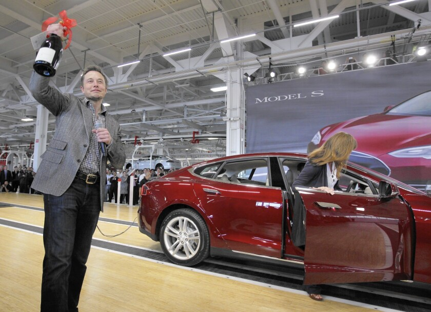 Tesla Motors Inc. CEO Elon Musk holds up a bottle of wine given as a gift from one of their first customers, right, during a rally at the Tesla factory in Fremont in July 2012.