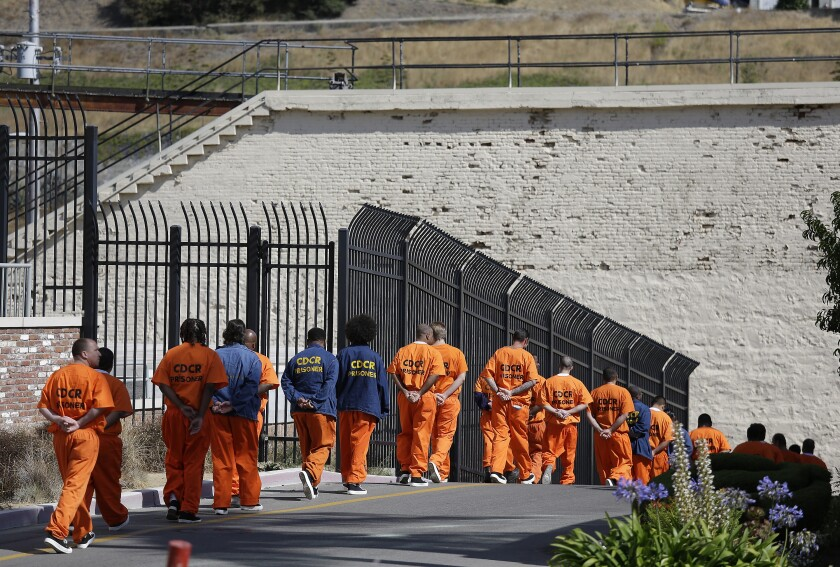 FILE - In this Aug. 16, 2016, file photo, a row of general population inmates walk in a line at San Quentin State Prison in San Quentin, Calif. California is giving 76,000 inmates the opportunity to leave prison earlier. They include violent and repeat felons. The move comes as the state aims to further trim the population of what once was the nation's largest state correctional system. More than 63,000 inmates convicted of violent crimes will be eligible for good behavior credits that shorten their sentences by one-third instead of the previous one-fifth under new rules that take effect Saturday, May 1, 2021. (AP Photo/Eric Risberg, File)