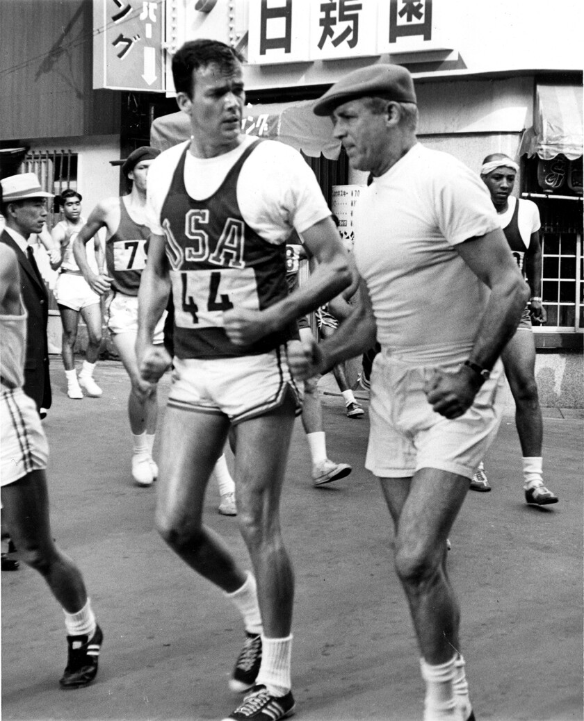 A black-and-white picture of a man, left, in an USA running uniform and a man in all-white gym clothes