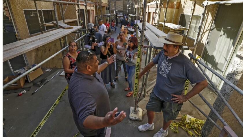 Gilbert Nunez, left, owner, of sandblasting company, talks to John Urquiza and other residents of a Highland Park apartment complex Marmion Royal,  picketing to block workers from sandblasting their courtyard.
