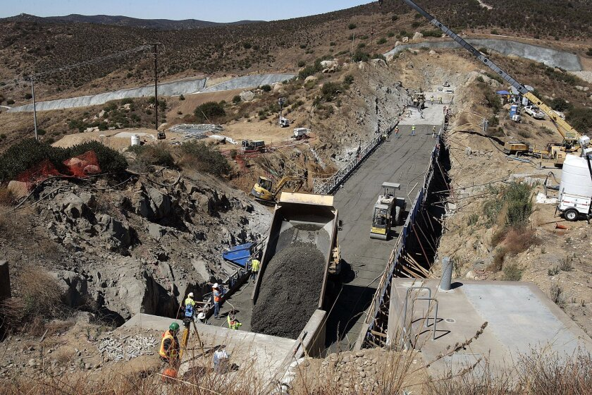 A dump truck releases its load of concrete atop a saddle dam at the San Vicente reservoir project in Lakeside. The concrete will be leveled to form another level of the saddle dam as part of a plan by the San Diego County Water Authority to raise the dam by 117 feet. When the work is completed in 2