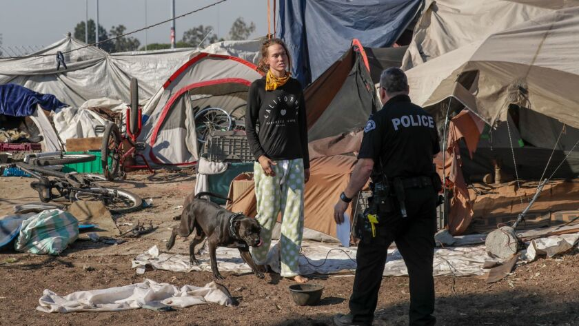A police officer speaks to a woman at a homeless encampment in Anaheim on Dec. 17, 2017.