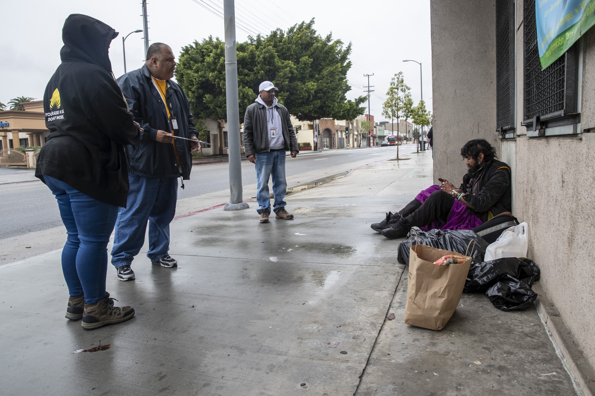 HOPICS outreach nurse Kenya Smith, right, Ralph Gomez, center, and Kat Johnson, left, leave a bag of food for Davis Soto, taking care to stay at least six feet away from him. The coronavirus pandemic has led to a list of new precautions that outreach workers must follow.