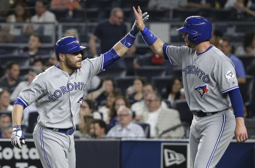 Toronto Blue Jays' Russell Martin, left, is greeted by Justin Smoak after hitting a two-run home run against the New York Yankees during the seventh inning of a baseball game Wednesday, May 25, 2016, in New York. (AP Photo/Julie Jacobson)