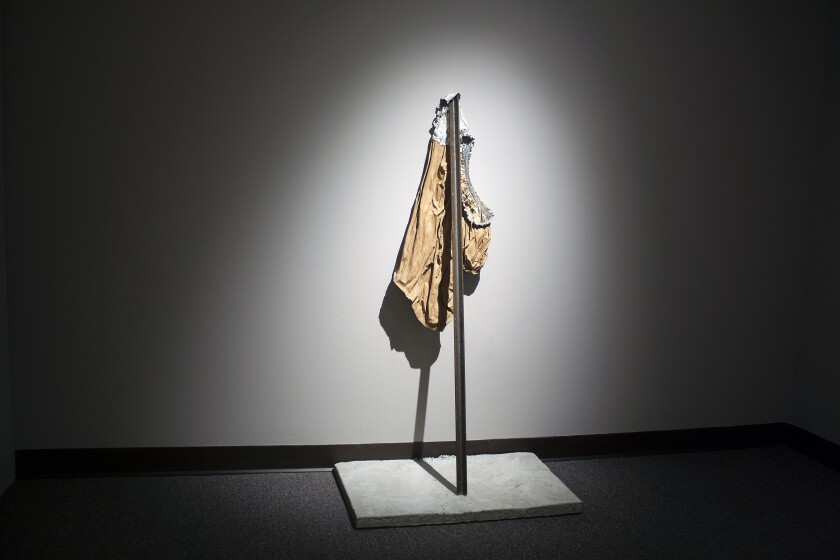 A dramatically illuminated photograph shows a woman's shirt held up by a steel fence post against a wall